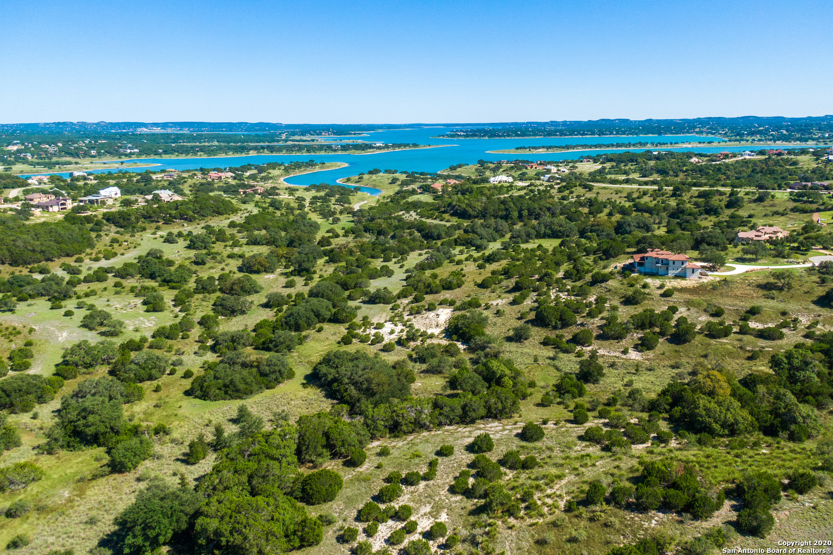 Unique and picturesque 4.59 acre lot with unlimited potential to build your dream home within the premier subdivision of Mystic Shores!  The topography is gently sloping to the back with an abundance of mature trees allowing for seclusion, while enjoying the peaceful hill country view from your back patio.  Lot offers a lake view to the East side of the property and panoramic country view from the back.  This is a one of a kind lake community with top notch amenities including clubhouse, community pool, tennis courts, private lake/river park, walking trails