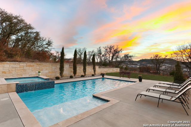 Spectacular custom-built hill country retreat in The Canyons at Scenic Loop situated on one-half acre with breathtaking views! Enter the home through the inviting foyer to observe the spacious open floor plan and elevated finishes throughout including hardwood and travertine flooring. The large, warm family room is the perfect gathering space with a floor to ceiling stone fireplace and soaring ceilings. The chef in the family will enjoy cooking meals in the kitchen with professional grade appliances and those meals can be feasted on in one of three dedicated eating areas - a formal dining room that can fit the entire family, a built-in breakfast nook, or a breakfast bar. A wet bar complete with wine refrigerator and ice machine along with the sizable pantry round out the downstairs common areas. Working from home can appreciated in the study with lots of natural light and hill country views. Spacious master suite with an expansive bedroom featuring a fireplace and outdoor access, a large spa-like bathroom with separate vanities, a deep soaking tub, walk-through shower, and separate his/her closets. The largest master closet with custom cabinetry is a fashionista's dream! A secondary bedroom with en-suite bath (currently a 2nd office) and a guest powder bath are also located downstairs. Make your way to the second floor on the formal staircase with hardwood floors and intricate wrought iron railings to the landing with room for a sitting area. A private guest suite with walk-in shower is perfect for visiting company. The fourth and fifth bedrooms, both with en-suite bathrooms, are also located on the second floor. Expansive game room, media room, and multi-functional niche that could be used as a workspace complete the upstairs and are the ideal places for the kids to play or for fun family games! There is abundant storage in every room with walk-in closets. The oversized three-care garage is ideal for the car enthusiast.  Outside the home is a private covered porch 